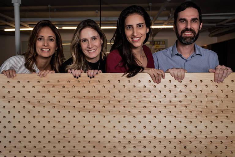 Os sócios Letícia Pettená, Carolina Mello, Rosana Fridman e Paulo Gontijo, um ao lado do outro, em frente a uma mureta de madeira clara