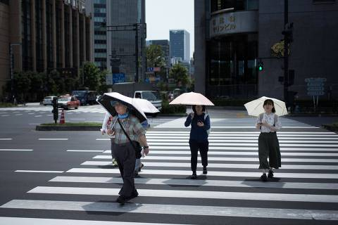 People hold umbrellas as they walk along a street in Tokyo on July 23, 2018, as Japan suffers from a heatwave.