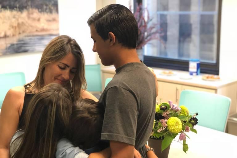A brasileira Jaene Silva de Miranda, 45, abraçada aos três filhos, de 8, 10 e 16 anos, depois de terem sido separados por quase dois meses na fronteira dos Estados Unidos
