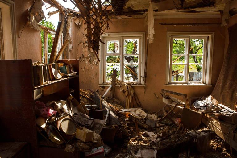 O local tem objetos diversos acumulados no chão, escurecidos pelo tempo e as explosões. Do lado esquerdo é possível ver parte do telhado e da parede partidos e algumas vigas de madeira caindo. No centro e à direita da imagem, há duas janelas, com vidros estilhaçados.