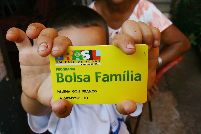 Criança segura o cartão verde e amarelo do bolsa família