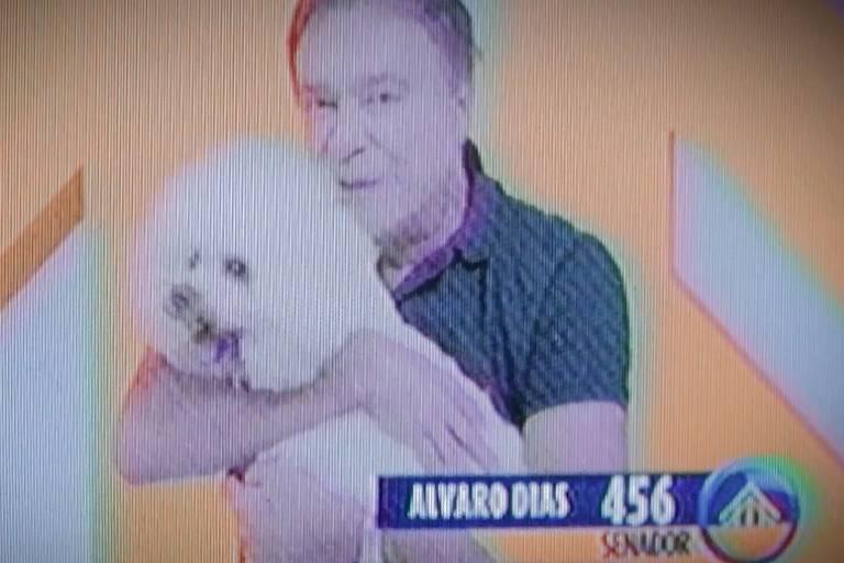 Alvaro Dias segura um cachorro em campanha ao Senado em 2014