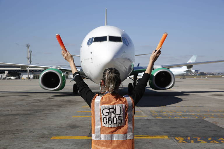 Avião em pista, com pessoa à sua frente, de costas