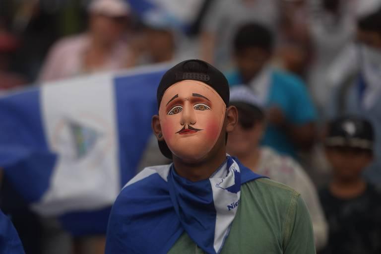 Close de homem usando uma máscara de borracha e uma bandeira da Nicarágua como lenço no pescoço
