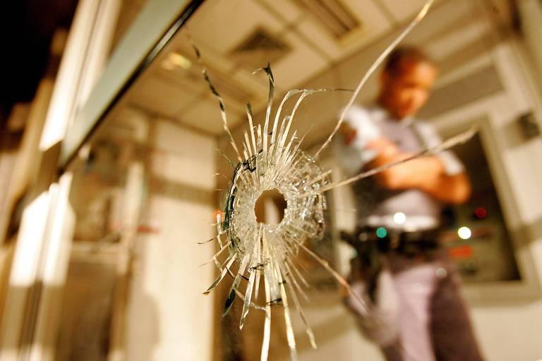 Marca de tiro em porta de vidro com PM ao fundo
