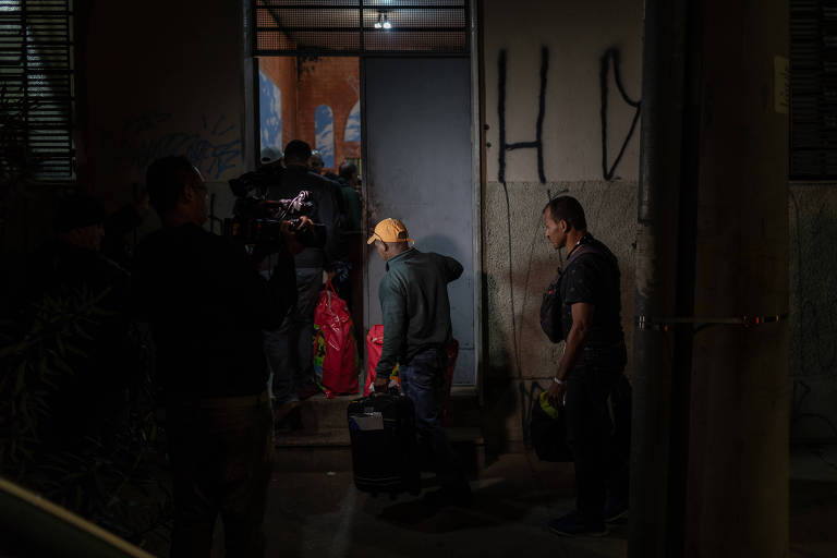 Três homens fazem fila com malas antes de entrar pela porta de ferro da casa.