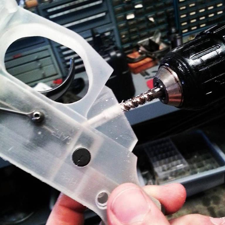 Homem segura pedaço da arma de plástico com a mão e usa furadeira para aparafusar peça metálica.