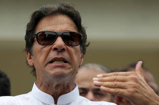 Cricket star-turned-politician Imran Khan, chairman of Pakistan Tehreek-e-Insaf (PTI), speaks to members of media after casting his vote at a polling station during the general election in Islamabad