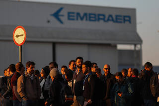 Employees of the Brazilian aviation company Embraer are seen in front of the factory in Sao Jose dos Campos