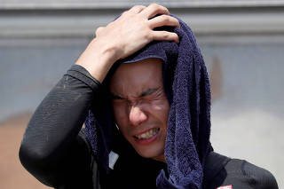 A volunteer, for recovery work, wipes his sweat as he takes a break in a heat wave at a flood affected area in Kurashiki
