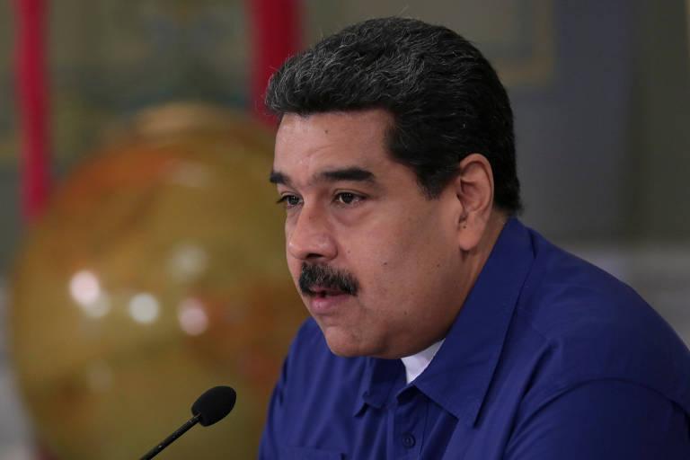 Maduro aparece de perfil, com o rosto para o lado esquerdo, falando em um microfone. Ele usa camisa azul e camiseta branca por baixo, está sentado e aparece apenas do peito para cima.