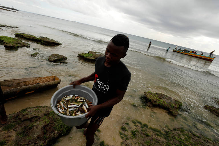 Homem leva peixes em uma bacia cinza ao chegar a uma praia com pedras. Ao fundo à direita é possível ver um barco pesqueiro com ao menos dez pessoas.