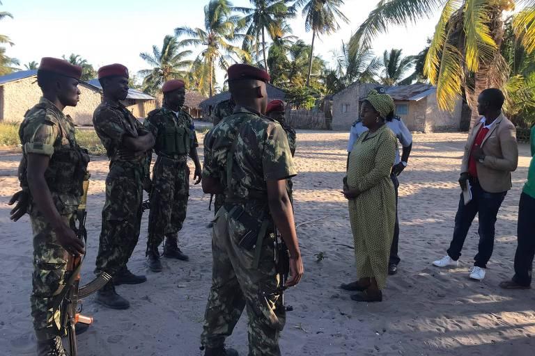 Cinco soldados com fardas de camuflagem verde e boinas vermelhas estão do lado esquerdo, enquanto uma mulher e dois homens a acompanham do lado direito