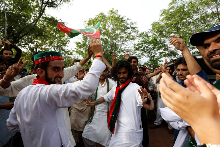 Apoiadores de Imran Khan comemoram do lado de fora de sua casa após seu discurso no qual se autodeclarou vencedor das eleições