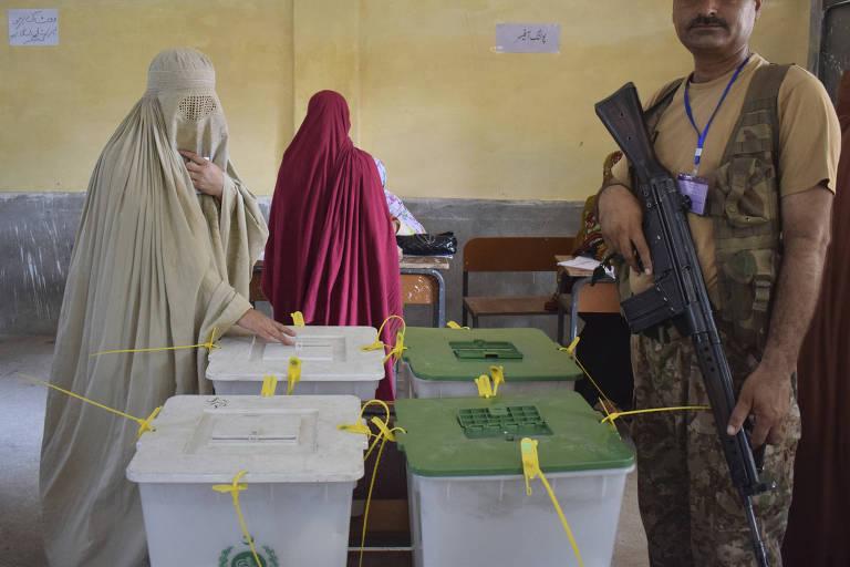 Mulher deposita voto em urna em Peshawar, no Paquistão