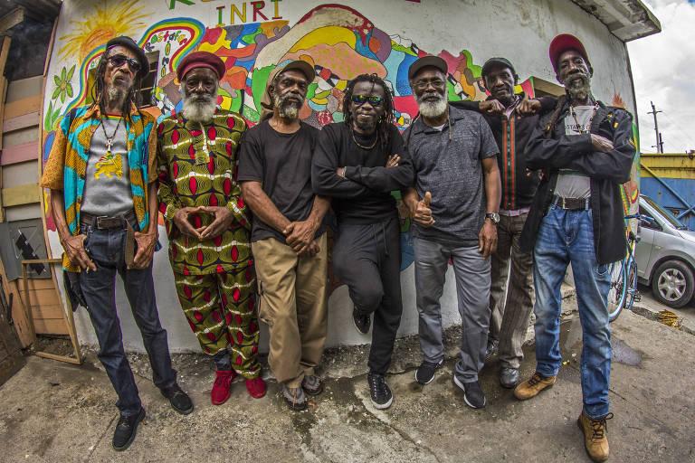 Artistas jamaicanos que fazem show-tributo ao filme 'Rockers' posam em frente a um grafite colorido