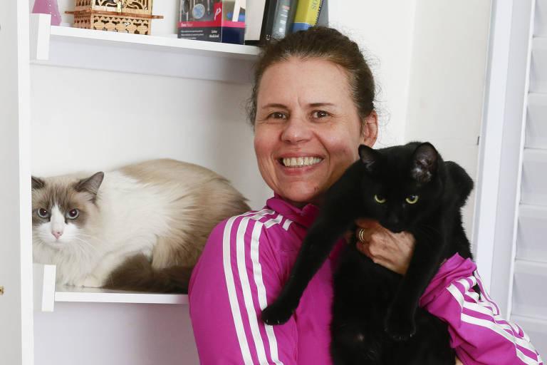 Érica Capistrano, 56, entre os gatos Nina (à esq.) e Yang