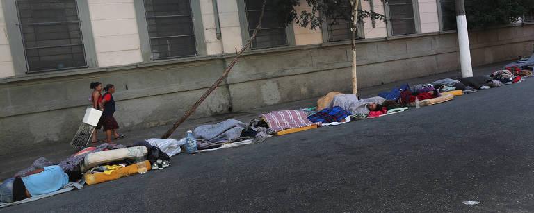 Pessoas dormem na calçada em colchões