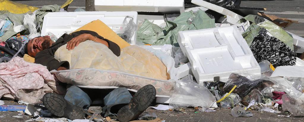 Morador de rua dorme sobre o lixo