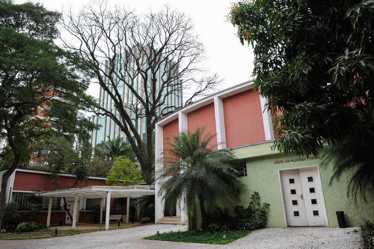 Área com árvores e uma casa verde e vermelha