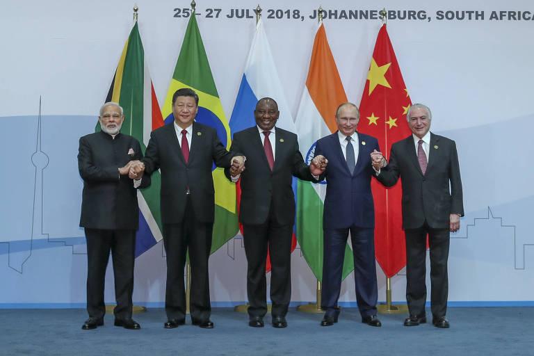 Os cinco líderes aparecem à frente das bandeiras dos cinco países, colocadas na seguinte ordem: África do Sul, Brasil, Rússia, Índia e China.