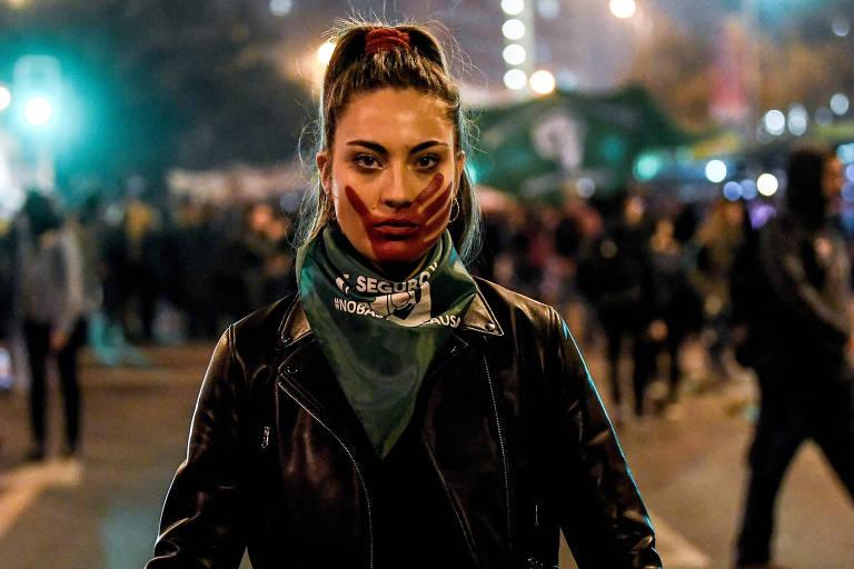 De roupa preta, mulher usa lenço verde no pescoço e pintou seu rosto com uma mão vermelha, simulando um tapa. Ao fundo, outras pessoas protestam.