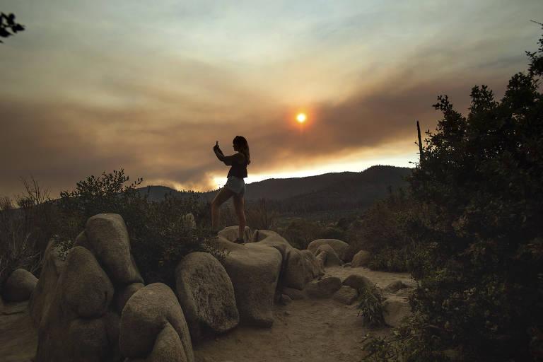 Mulher está em cima de uma pedra, vizinha a outras similares, enquanto posiciona o celular para tirar uma selfie. Ao fundo, é possível ver uma nuvem de fumaça cobrindo o sol.