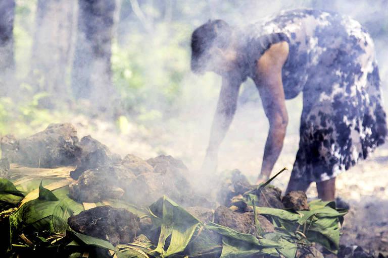 Índia da aldeia Kyikatêjé, na região de Marabá (PA), prepara o berarubu, carne assada com massa de mandioca em forno de terra (Augusto Dauster - 27.nov.15/Folhapress)