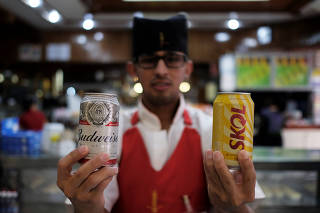 Waiter poses holding beer cans inside a bar in Sao Paulo