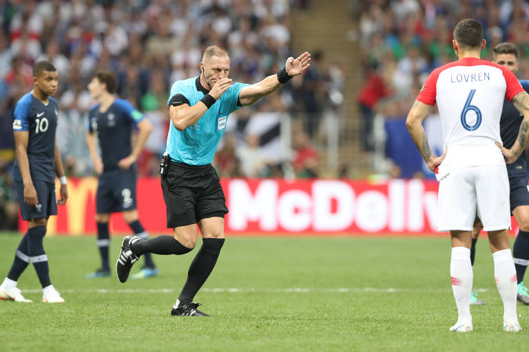 Árbitro da final da Copa do Mundo estica o braço para marcar pênalti para a França, após consulta ao árbitro de vídeo