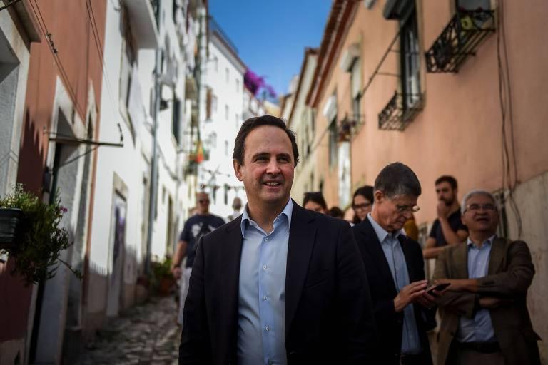 Fernando Medina, de terno azul sem gravata, sorri para a câmera em uma ruela estreita de casas cor de salmão, com pessoas ao fundo