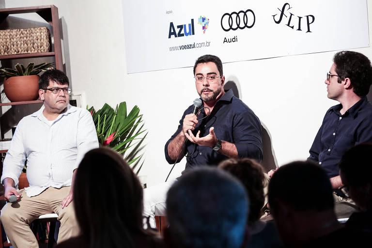 Marcelo Bretas falando ao microfone ao lado de debatedores