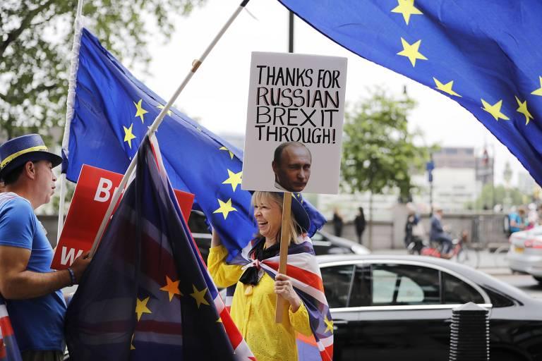 """Enrolada em bandeira britânica, mulher carrega cartaz com mensagem em inglês: """"Obrigado pelo brexit russo"""". Ao fundo, outras pessoas carregam bandeiras da União Europeia."""