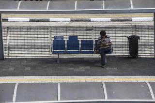 Homem sozinho aguarda ônibus no centro de São Paulo