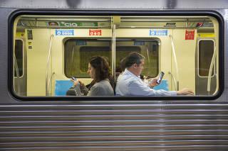 Passageiros usam o celular dentro do metrô