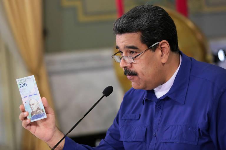 O ditador venezuelano Nicolás Maduro segura nota da nova moeda do país, que terá cinco zero a menos que a atual