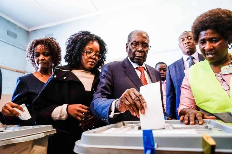 O ex-ditador Robert Mugabe (centro), vota acompanhado por familiares na capital, Harare