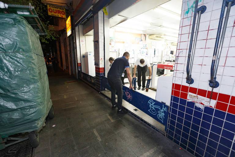 Funcionários fecham porta de loja na rua Teodoro Sampaio, em Pinheiros (zona oeste)