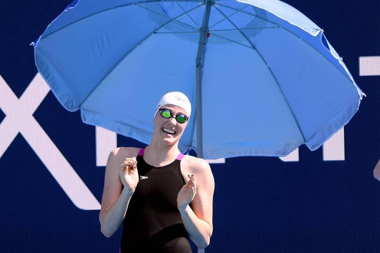 A nadadora americana Missy Franklin ri embaixo de um guarda-sol durante a seletiva americana