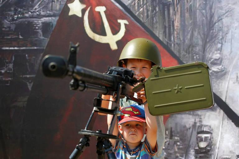 Crianças brincam com metralhadora soviética em feira em Alabino, nas cercanias de Moscou
