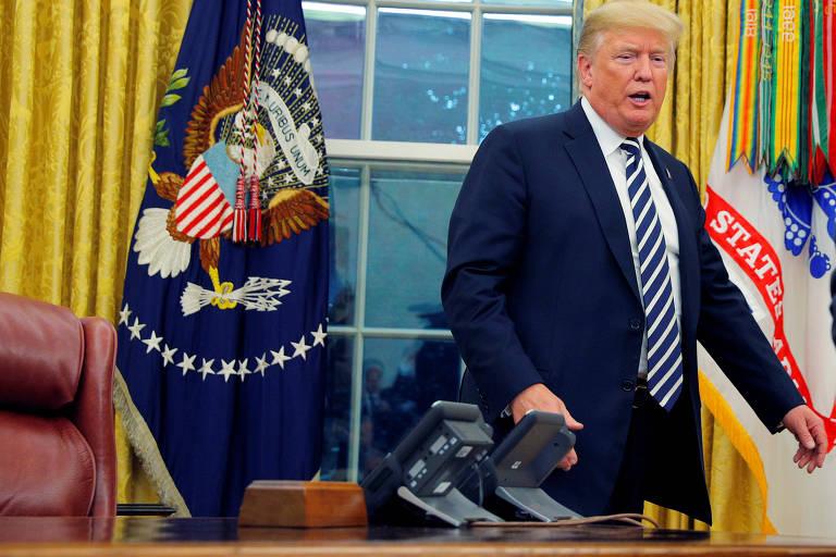 Trump aparece por trás da mesa, que aparece na parte de cima, com dois telefones e parte de sua poltrona, vermelha. A janela é coberta pela metade com cortinas amarelas e, em cada ponta há bandeiras da Presidência dos EUA.