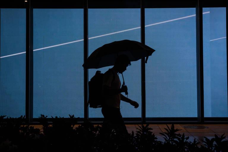 Depois de um longo tempo sem chuva, voltou a chover em São Paulo. Na foto, pedestre caminha com guarda-chuva em frente ao shopping JK Iguatemi, na Vila Olímpia, zona oeste da cidade