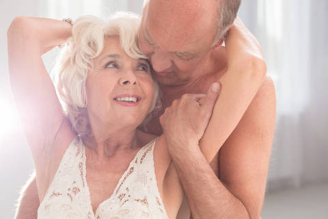 Passionate mature couple smiling and embracing each other, light interior. Credito  Photographee.eu / Fotolia