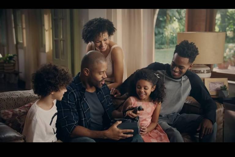 pai recebe perfume de presente. Familia está sentada no sofá: mulher atras, menino à esquerda, menina com vestido rosa e laço no cabelo à direita, e um jovem adolescente, à direita da menina