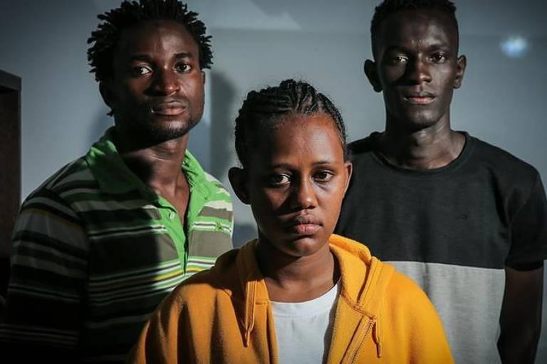 Três refugiados portugueses olham para a câmera, com mulher na frente e dois homens atrás