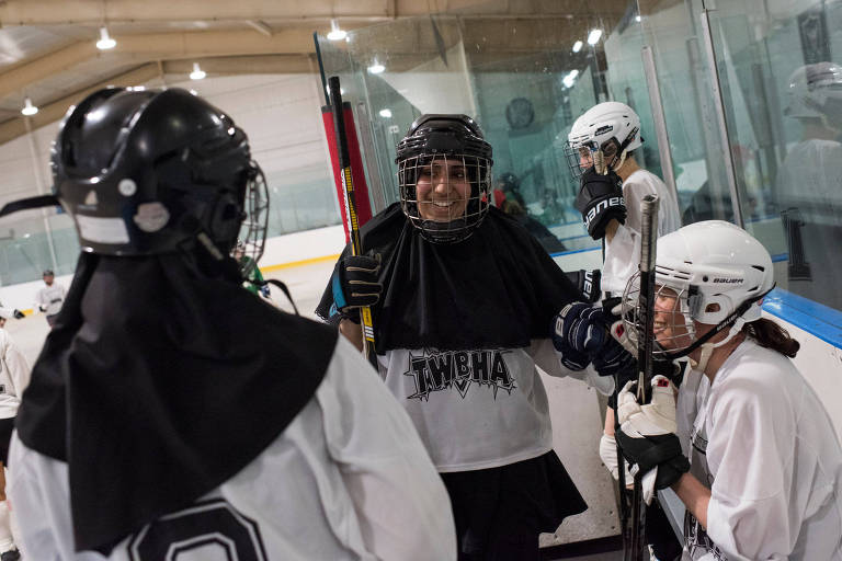 No centro, Asiyah Azmi conversa com colegas de equipe durante um jogo