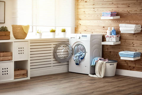 Interior of a real laundry room with a washing machine at the window at home Foto: JenkoAtaman / Fotolia  ÁREA DE SERVIÇO