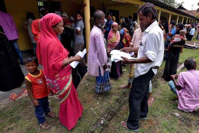 De camisa branca e calça cinza, homem verifica documentos de uma mulher que está à sua esquerda, usando vestido e lenço rosa de cabeça e com um menino de calça jeans e camiseta vermelha atrás dela. Eles aparece ao lado de uma fila com mais de 30 pessoas.