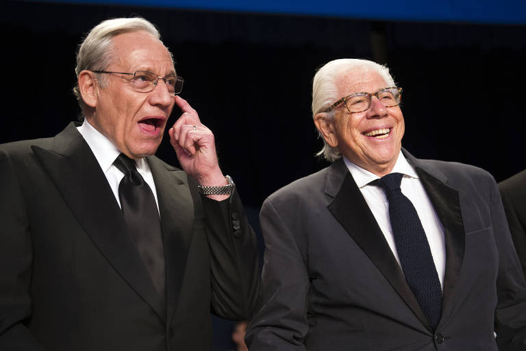 O jornalista Bob Woodward sorri e coça o olho ao lado de Carl Berstein, que gargalha, ambos de terno e gravata