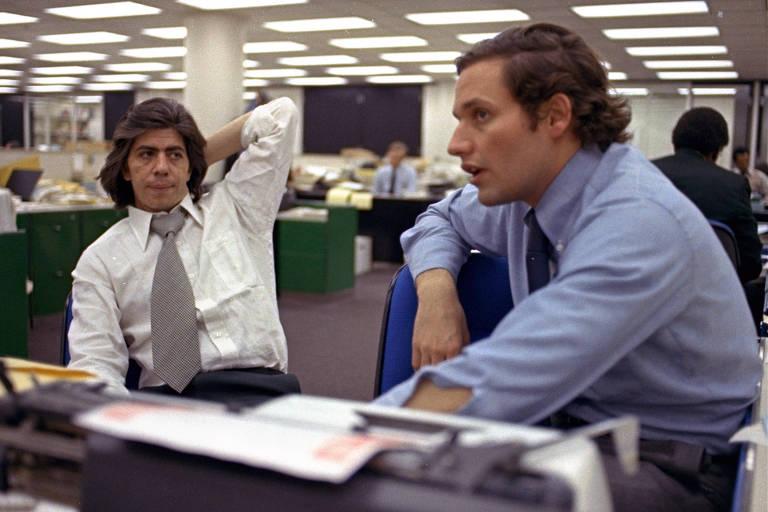 Carl Berstein, ainda jovem, coça a cabeça e conversa com Bobv Woodward, visto de perfil, em uma escrivaninha no meio da sala de redação do Washington Post